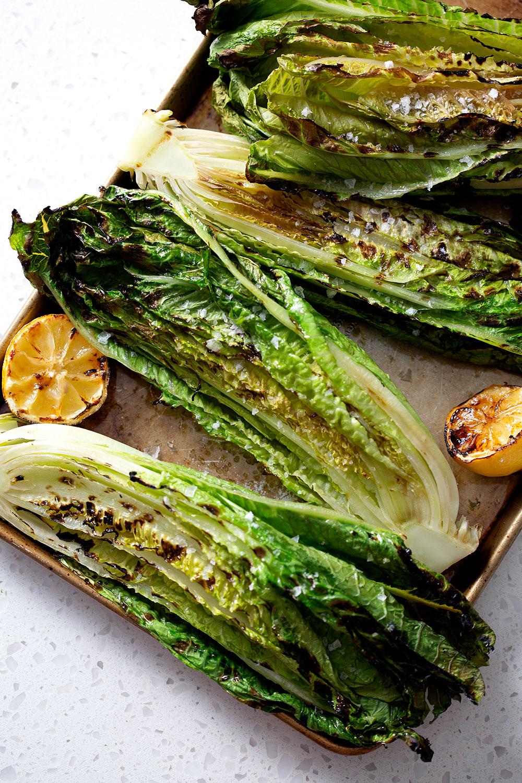 grilled romaine lettuce halves on baking sheet