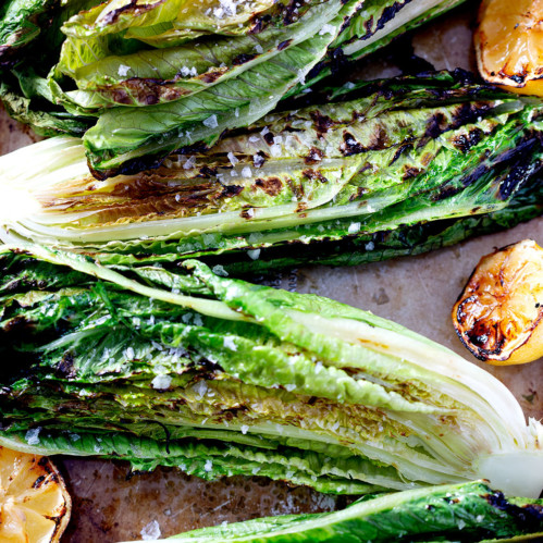 grilled romaine lettuce halves on baking sheet with grilled lemons