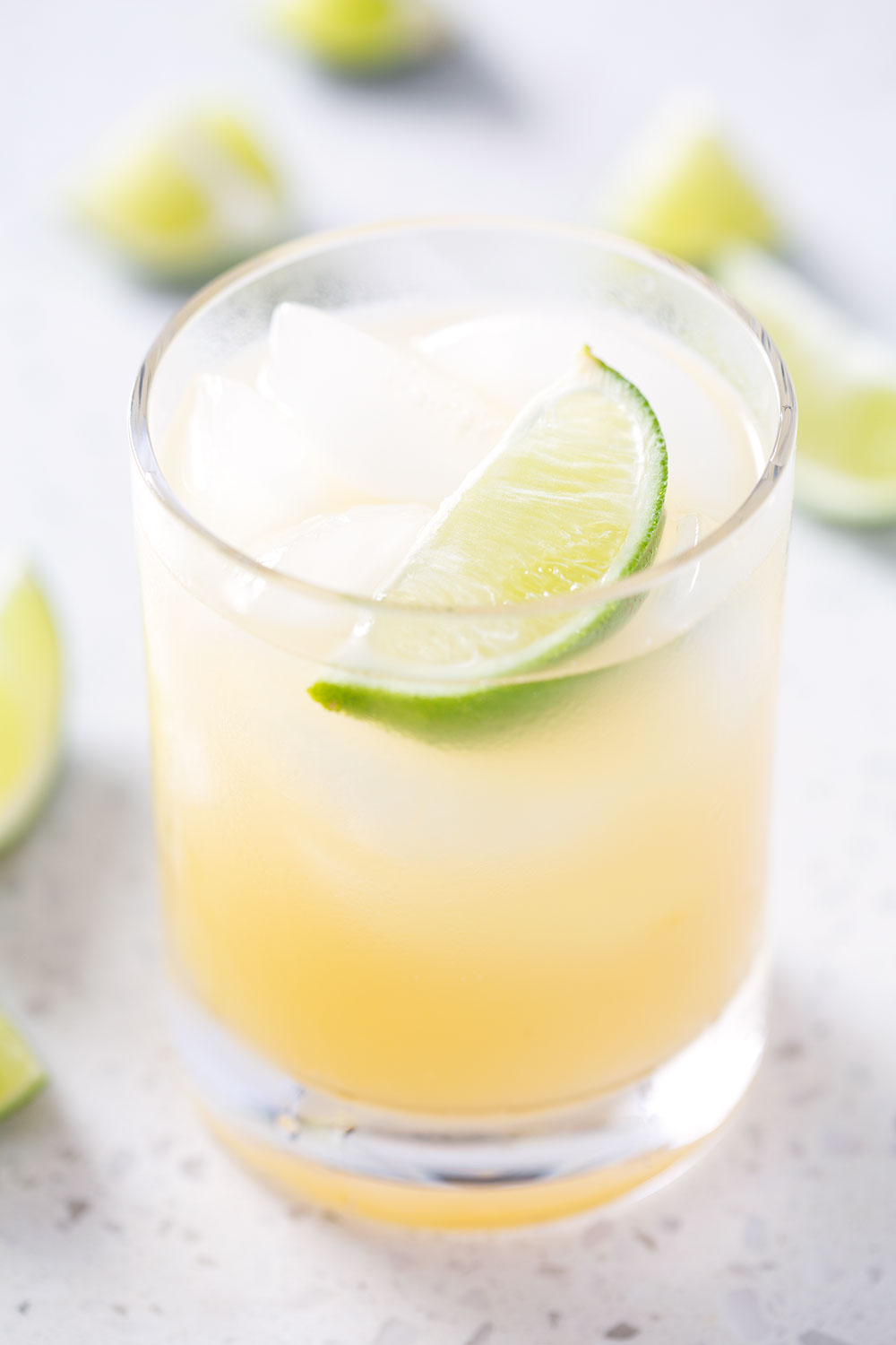 tumbler glass filled with a cocktail and garnished with a lime