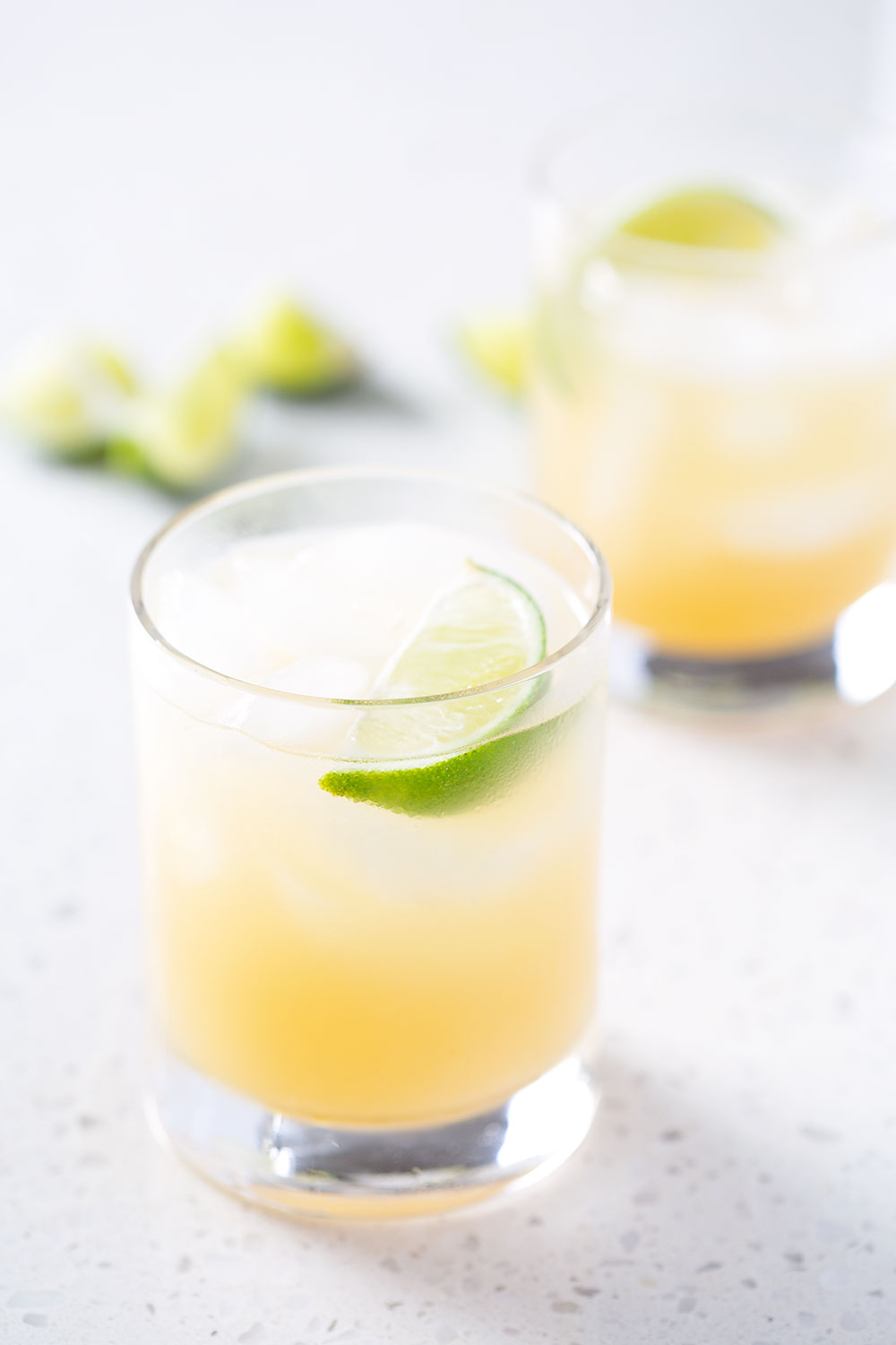 two cocktail and limes on white background