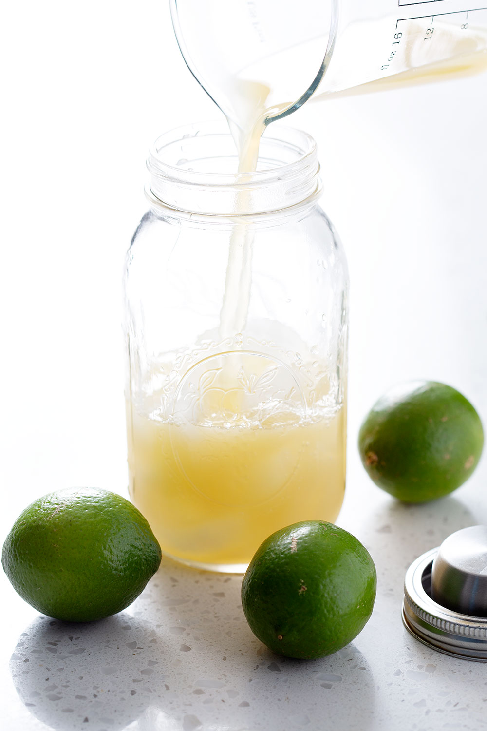 filling cocktail shaker with limes in front