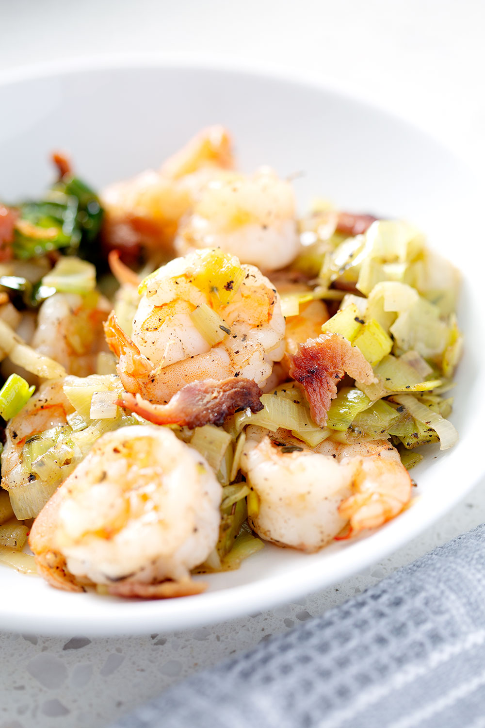 shrimp and onions on white bowl with napkin