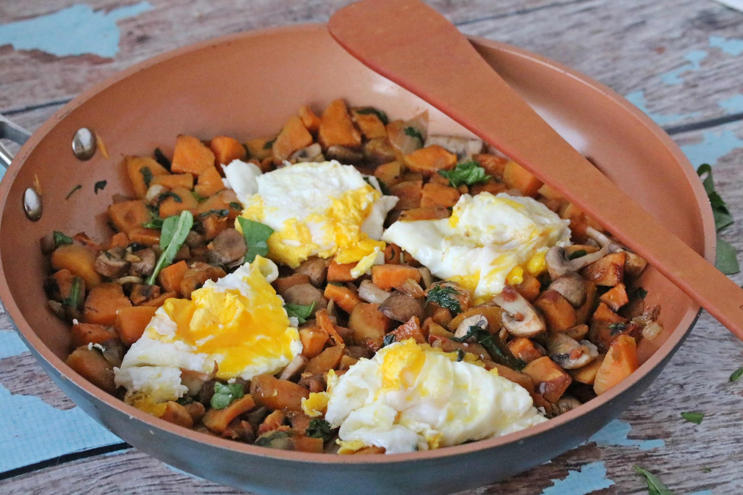 Breakfast sweet potato hash in a pan topped with eggs