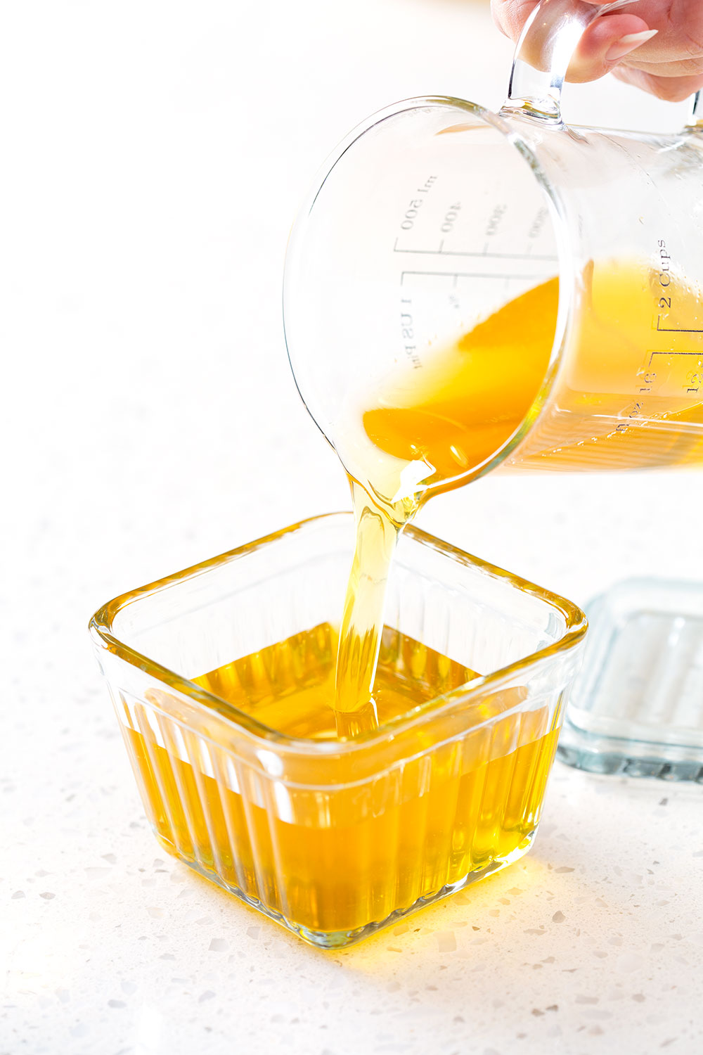 pouring melted homemade ghee into a glass butter dish