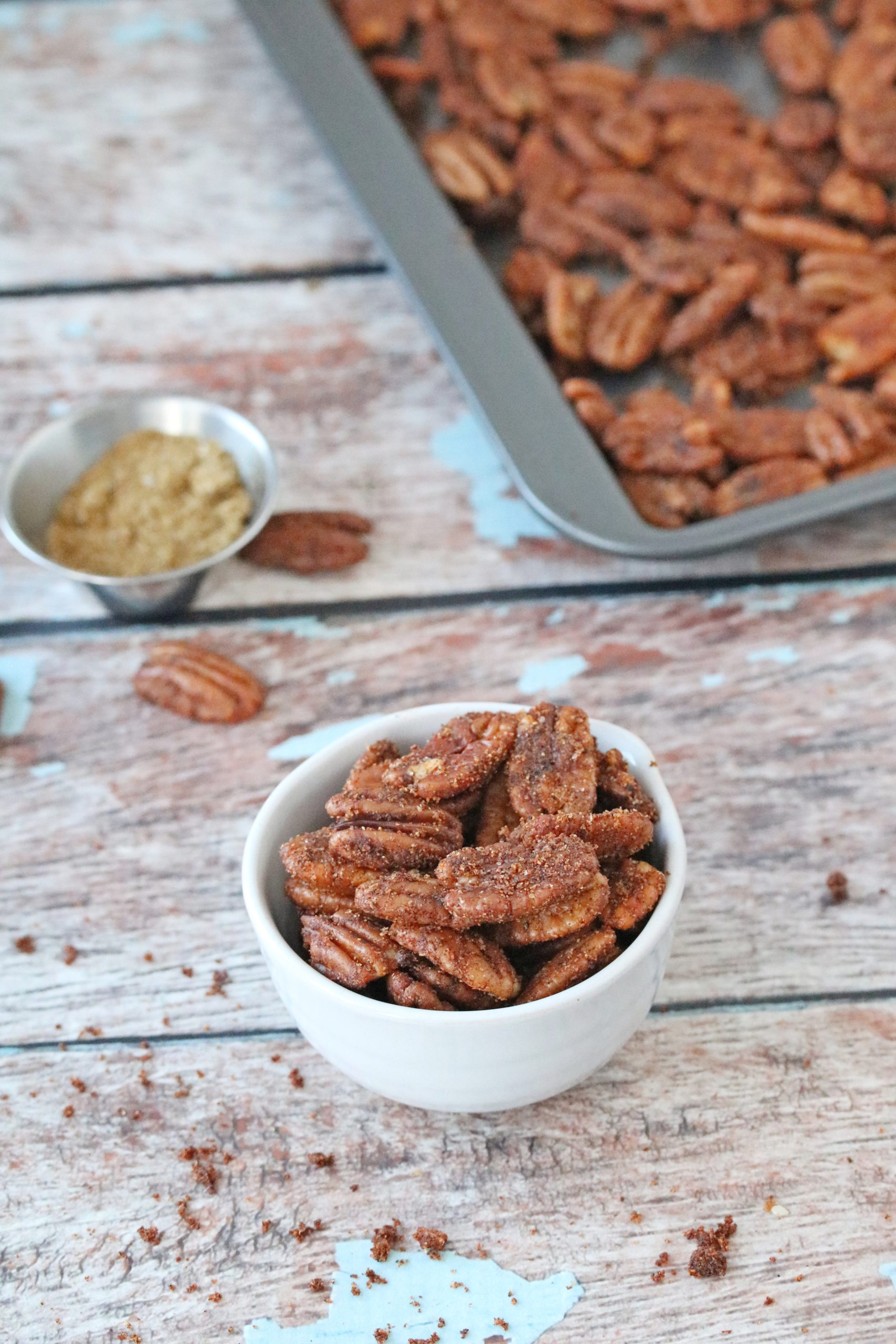 Cajun pecans in a white bowl with pecans on a tray behind it