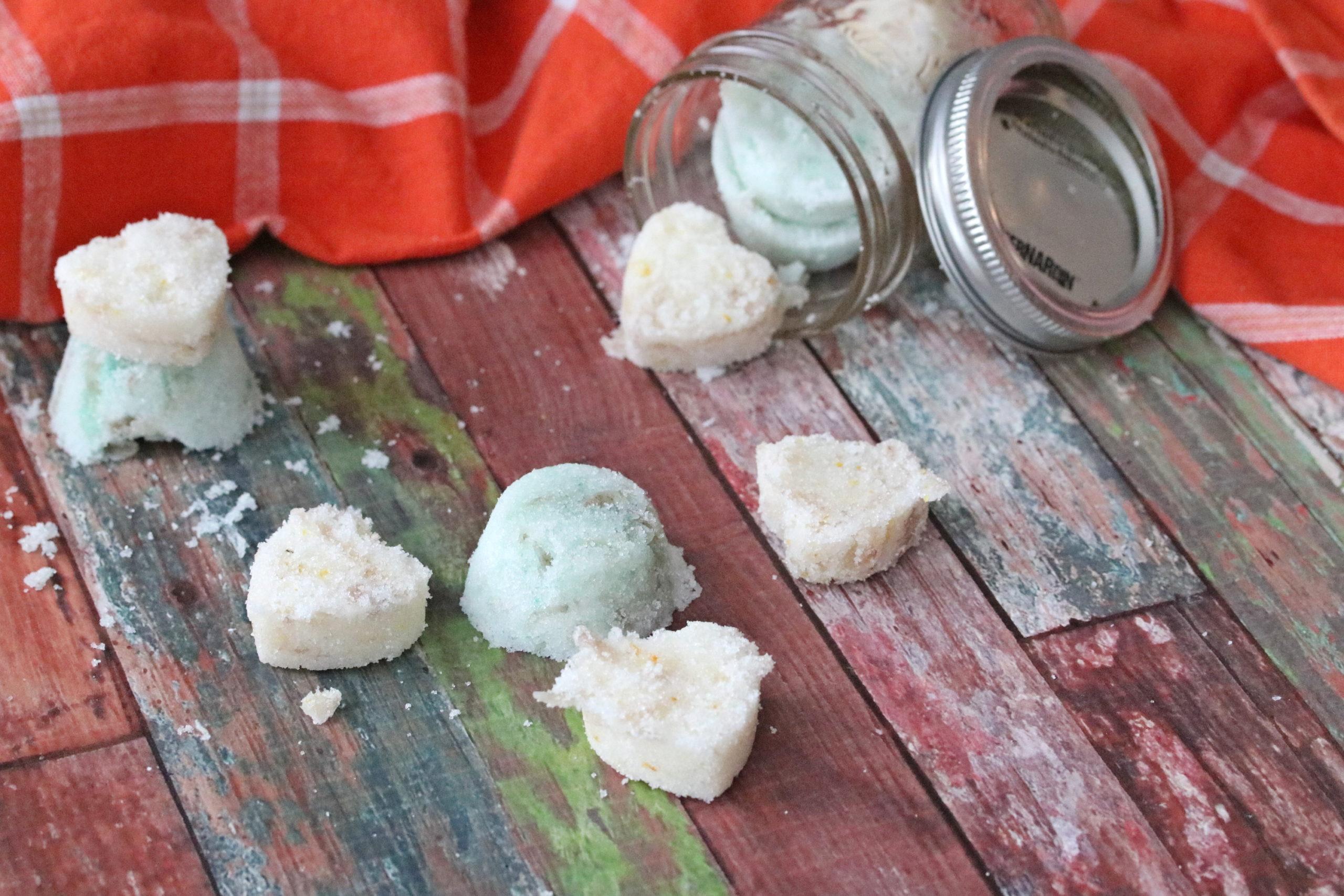 Diy sugar scrubs with a jar of scrubs behind them