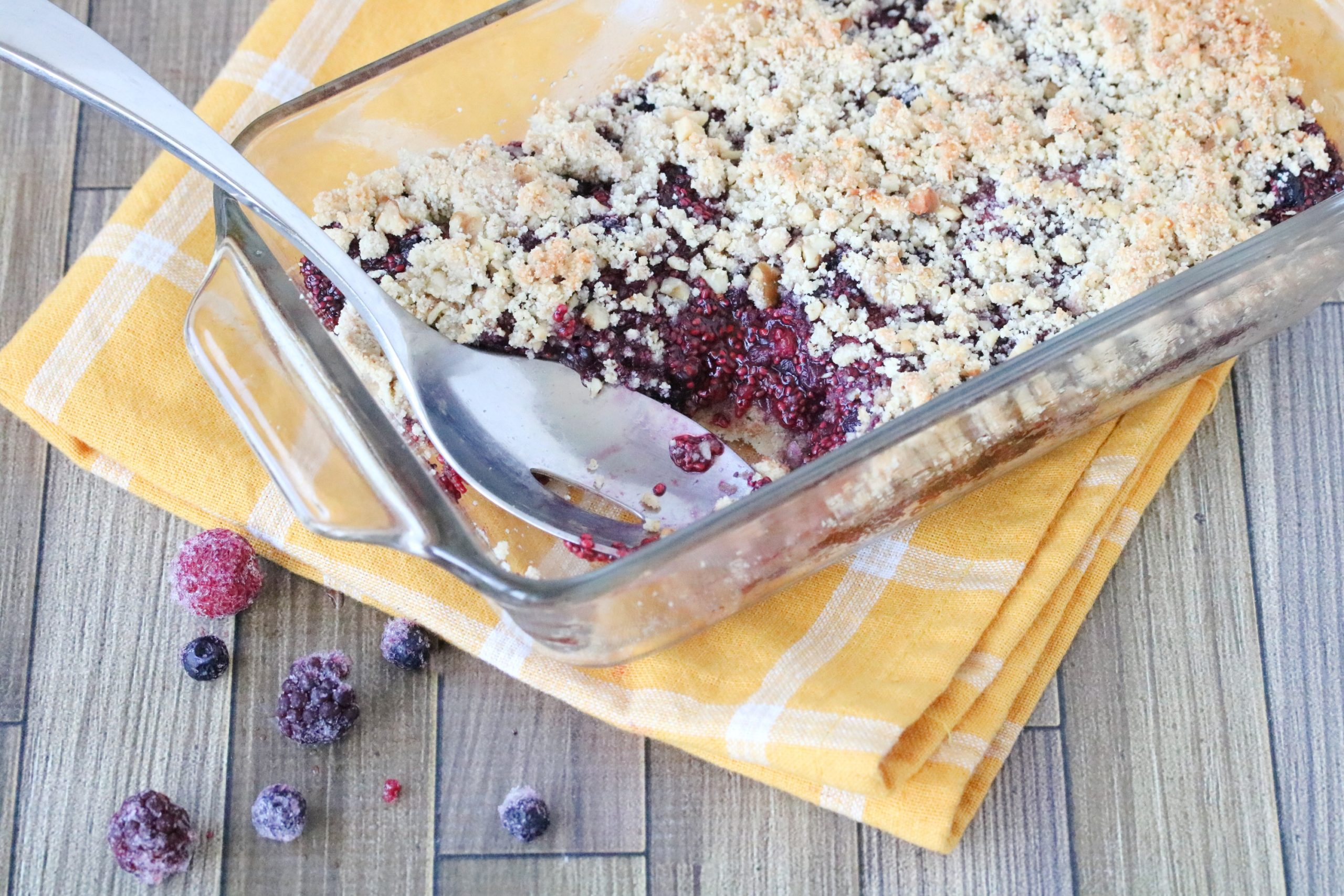 Easy berry crumble in cooking pan with a spoonful missing and a serving spoon in the pan on a yellow napkin