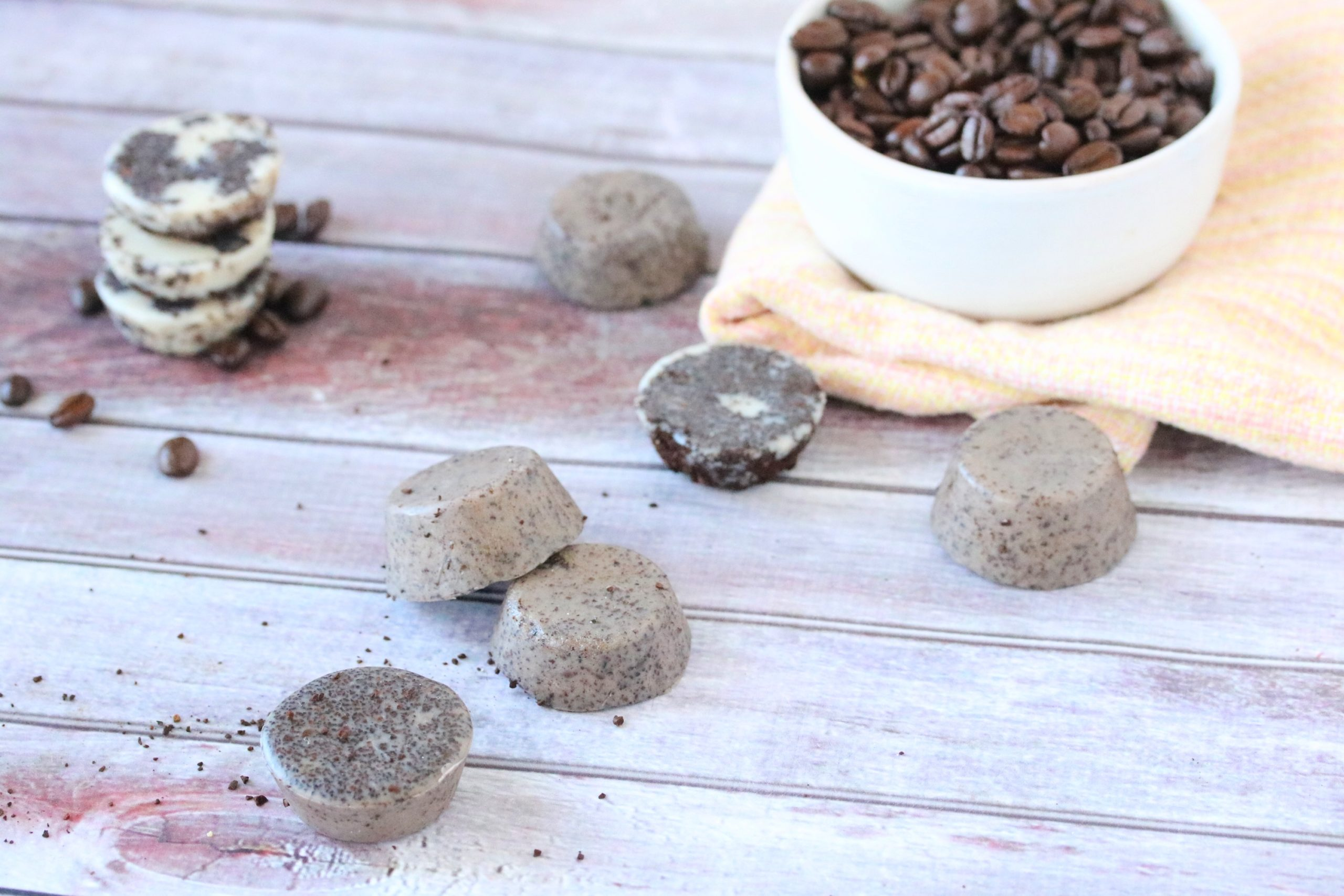 Exfoliating DIY lotion bars, three on the table with coffee grounds and bars stacked behind it with a bowl of coffee beans