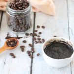 DIY coffee face scrub in a white bowl with coffee beans behind it