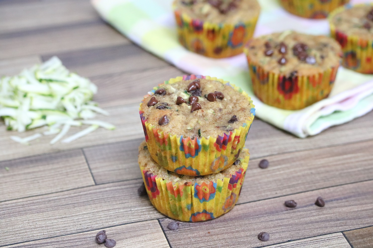 Two chocolate chip muffins stacked with shredded zucchini behind them and more muffins on a linen