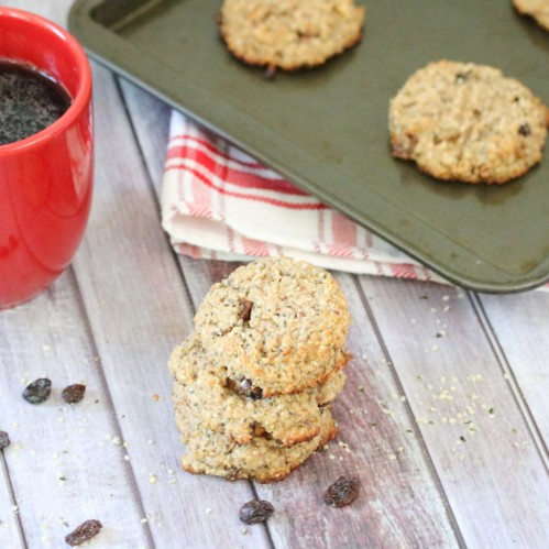 Breakfast cookies with raisins around them, a red mug with coffee and more cookies on a tray behind them