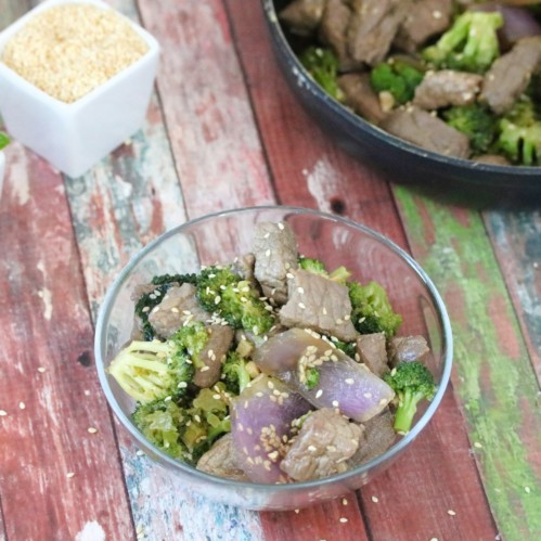 Beef and broccoli stir fry topped with sesame seeds in a glass bowl with sesame seeds and green onions in white dishes beside it and a pan with the remaining stir fry behind it