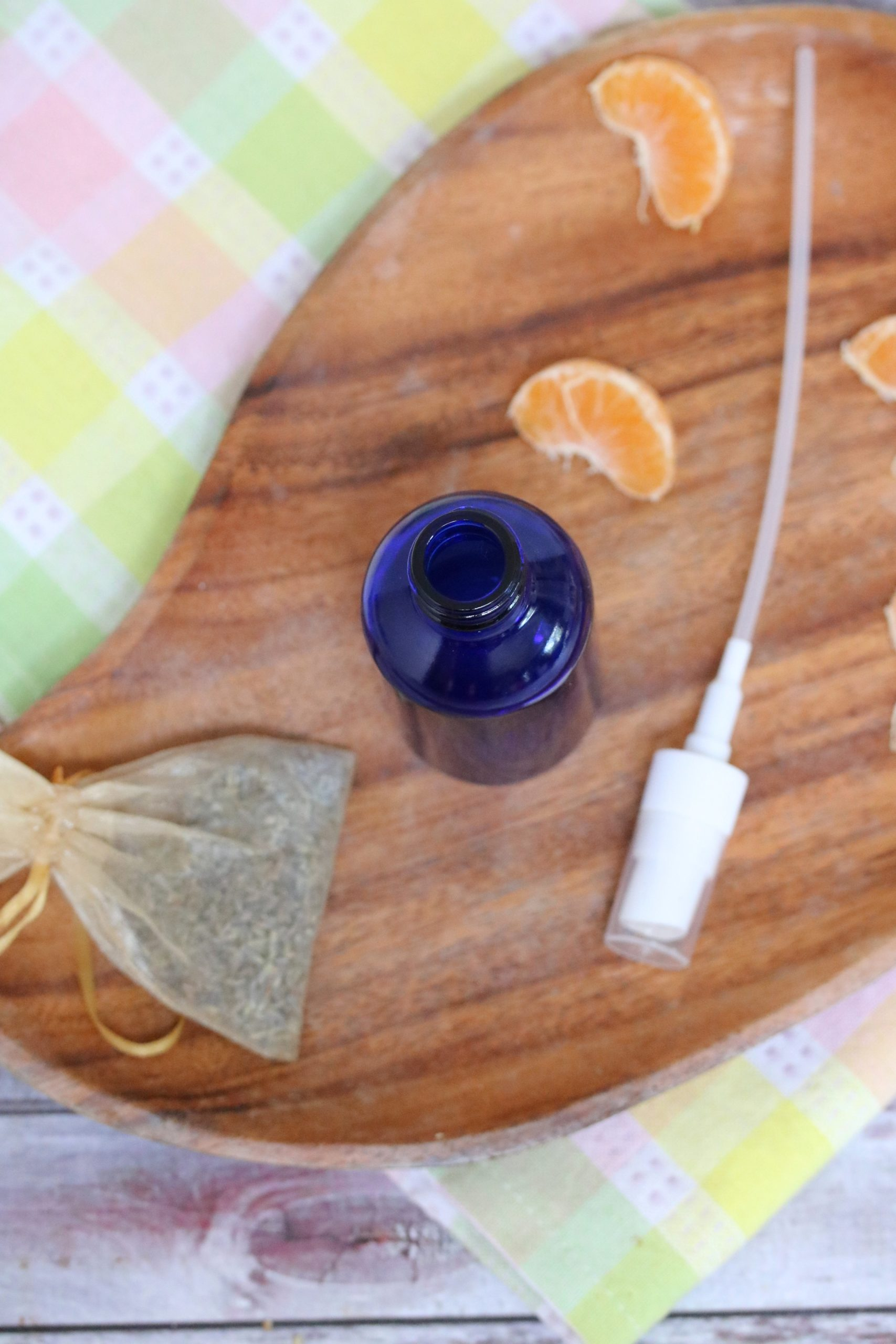 Blue glass bottle on a wooden cutting board on top of a colored linen with spray nozzle beside it. Orange slices and a bag of lavender around beside the spray bottle.