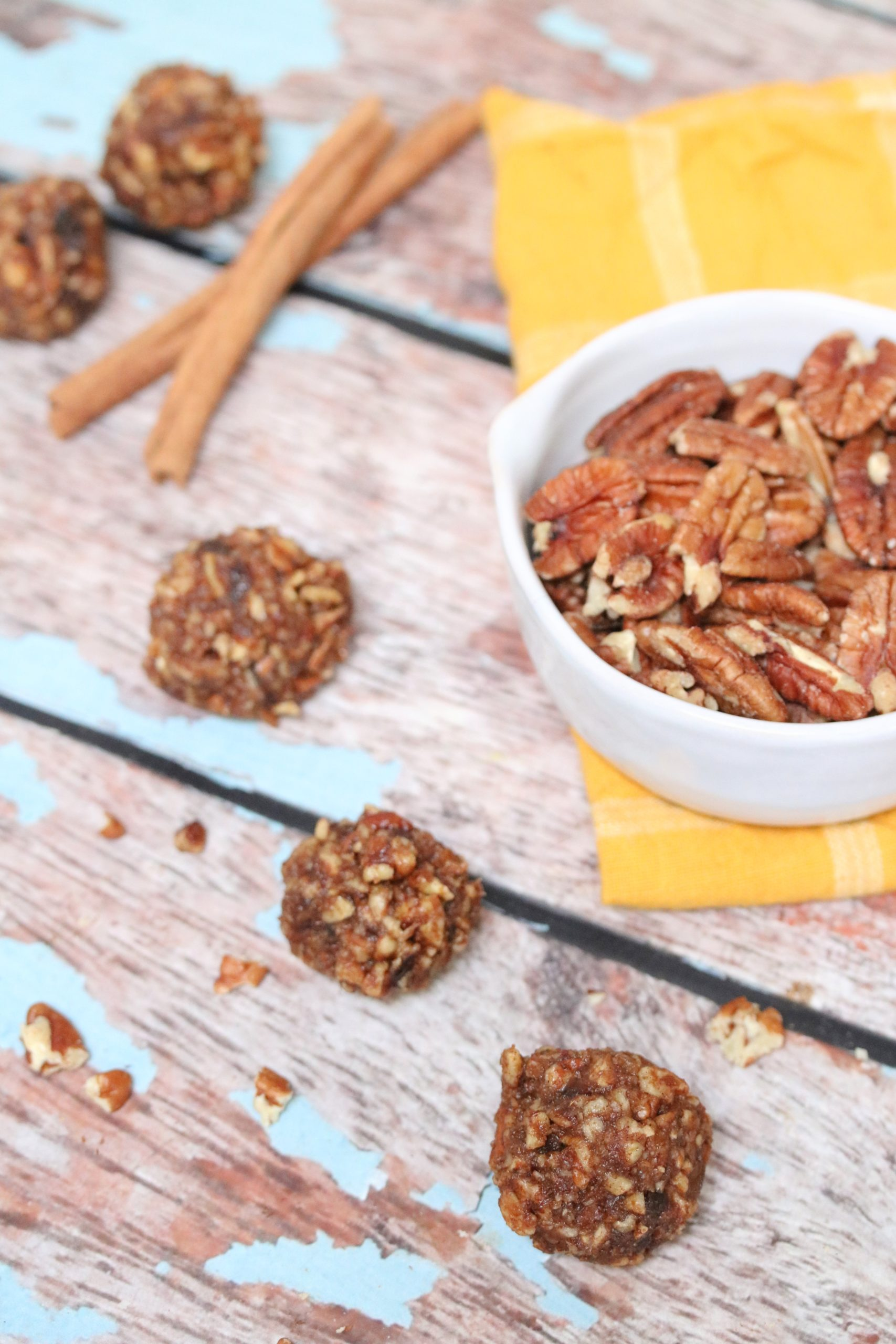 Three no-bake pecan balls in front of a bowl with pecans on a yellow cloth and cinnamon sticks behind it