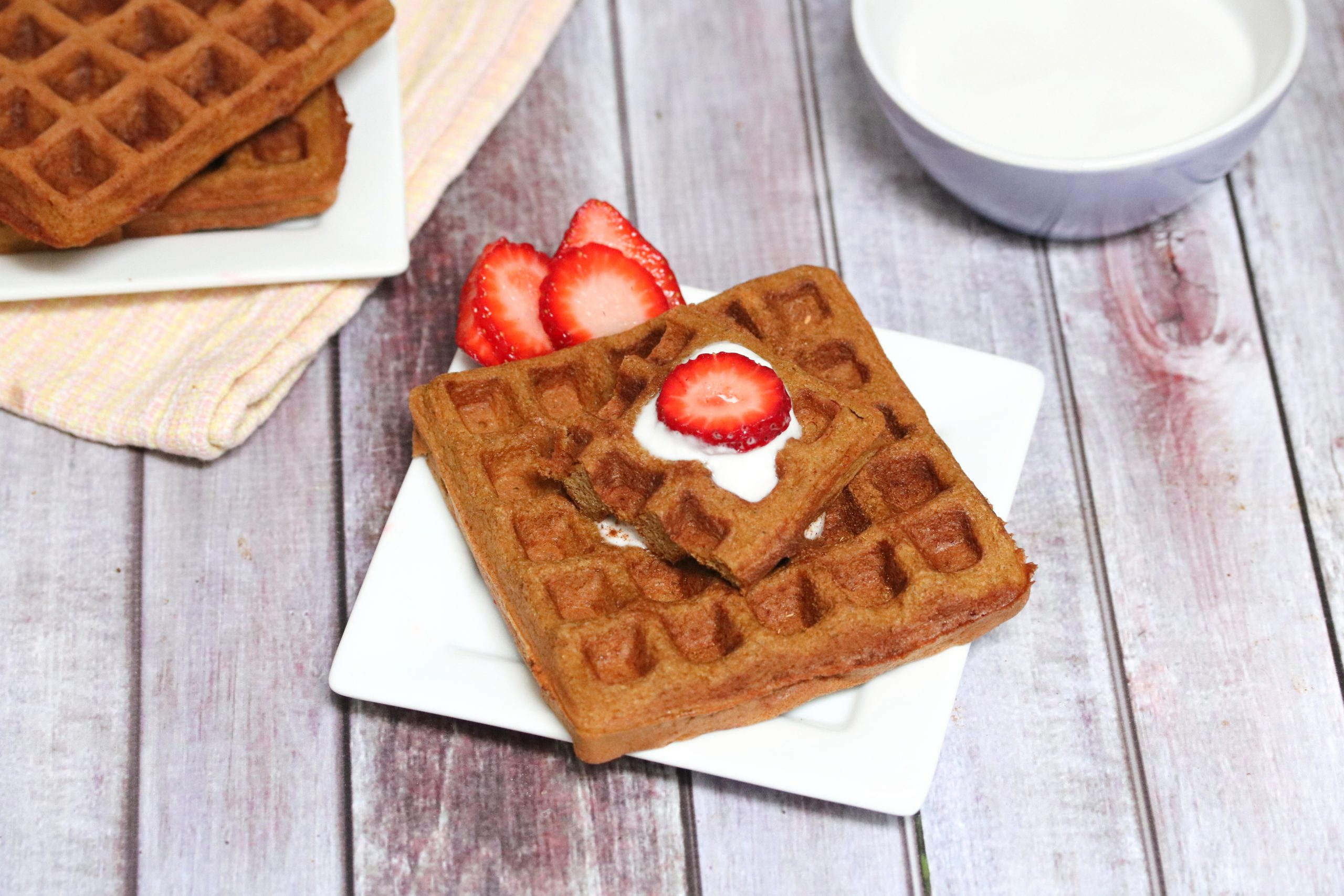 Square gingerbread waffle on a white plate with coconut milk and strawberries on top and more waffles and coconut milk behind it